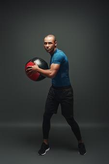 Rispetta l'allenamento del giovane sportivo in piedi su uno sfondo scuro con una palla in mano