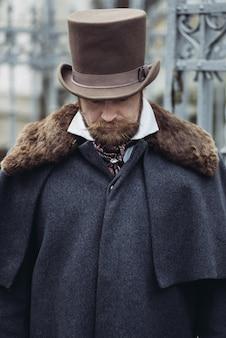 Rispettabile uomo baffuto in abiti classici retrò, cappotto e cappello.