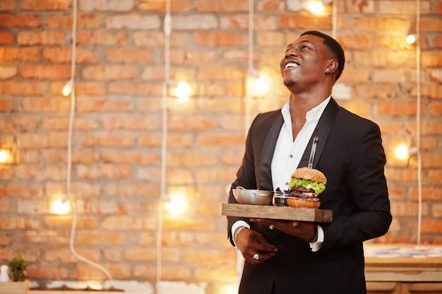 Il giovane soddisfatto rispettabile in vestito nero tiene il vassoio con doppio hamburger contro il muro di mattoni del ristorante con le luci