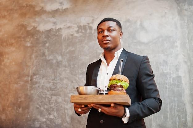 Il giovane rispettabile in vestito nero tiene il vassoio con doppio hamburger contro la parete grigia