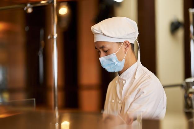Personale responsabile della cucina che utilizza la maschera respiratoria durante il lavoro