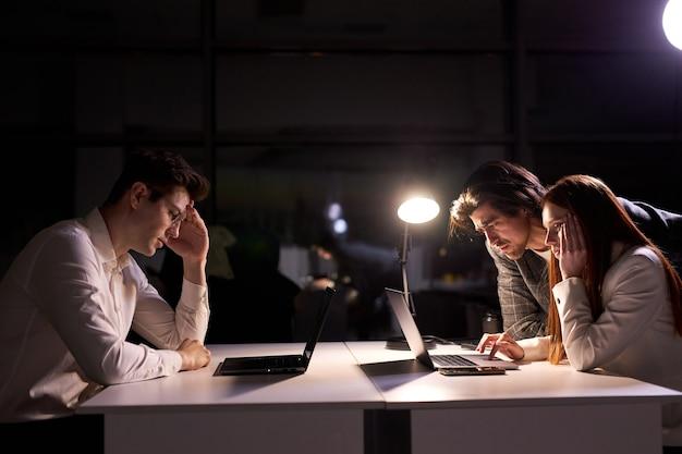 Il direttore reattivo o il manager dell'azienda aiutano i colleghi a rispettare la scadenza, non avendo tempo per dormire e riposarsi, vista laterale sugli uomini d'affari che lavorano insieme al progetto di avvio, utilizzando il laptop