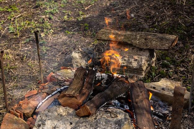 Riposare in giardino nella natura, preparare un fuoco per fare un barbecue, fuoco dal legno di ciliegio