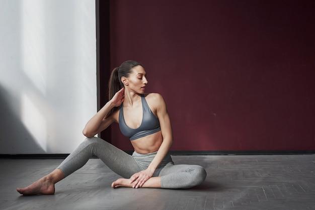 Riposo tra gli allenamenti. piuttosto giovane donna con una bella forma del corpo fitness si siede sul pavimento della stanza spaziosa