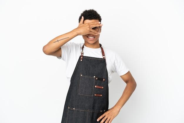 Ristorante cameriere afroamericano uomo isolato su sfondo bianco che copre gli occhi con le mani e sorridente