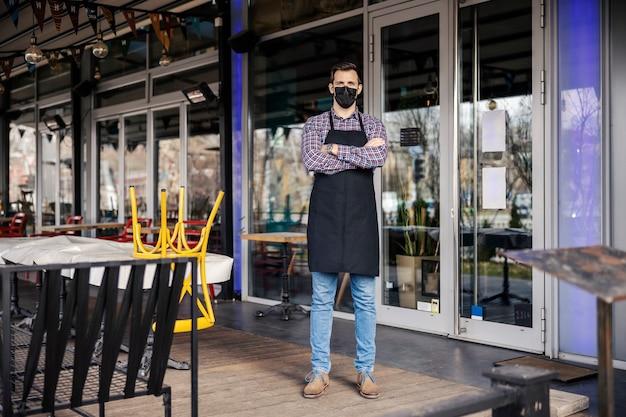 Ristorante chiuso per situazione epidemiologica di coronavirus. ritratto di un cameriere maschio in una camicia a quadri e grembiule con una maschera protettiva in piedi di fronte a un ristorante con le braccia incrociate