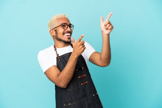 Ristorante cameriere colombiano uomo isolato su sfondo blu che punta con il dito indice una grande idea