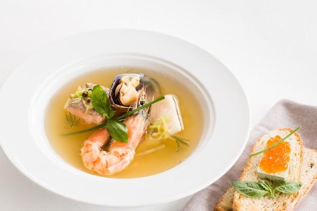 Cucina del ristorante. piatto di zuppa di pesce e panino al caviale al formaggio