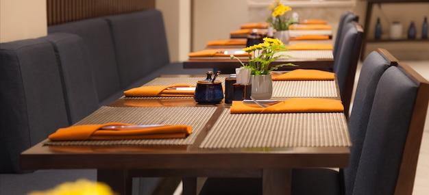 Tavoli ristorante con tovagliette, posate e tovaglioli