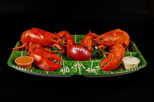 Cibo da ristorante per partry della partita di football americano. aragoste rosse sulla zolla verde con la palla.