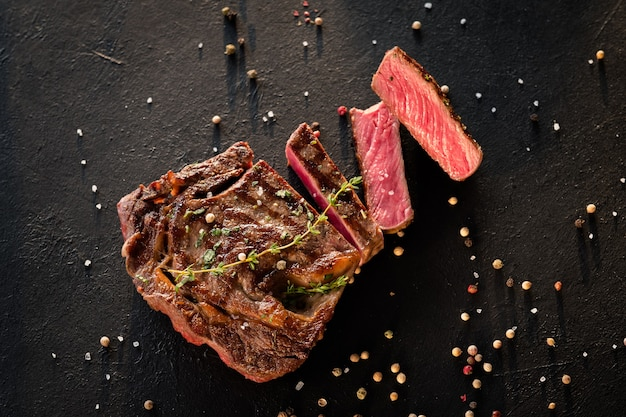 Arte del cibo del ristorante. bistecca alla griglia affettata sul nero strutturato