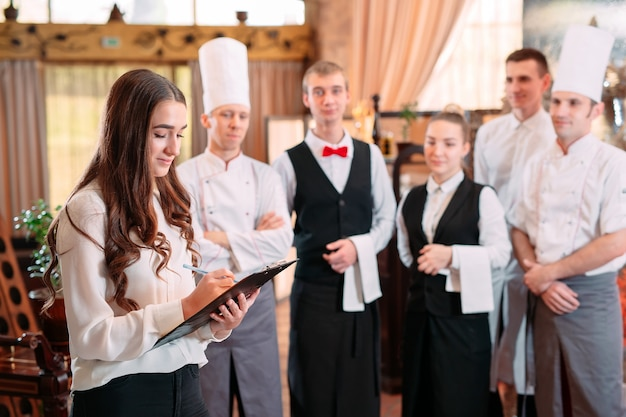 Direttore del ristorante e il suo staff in cucina. interagendo con lo chef in cucina commerciale.