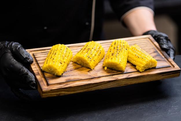 Menù del ristorante. ritagliata colpo dello chef che tiene tavola di legno rustica con mais bonduelle dolce al forno su pezzi di pannocchia.