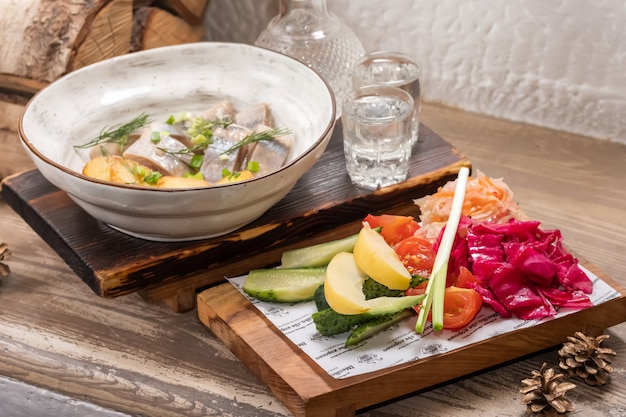 Ristorante menu di pesce con aringhe salate con anelli di cipolla e patate a cubetti bollite su un elegante piatto da ristorante con set di vodka fredda alcolica e salamoia assortita.