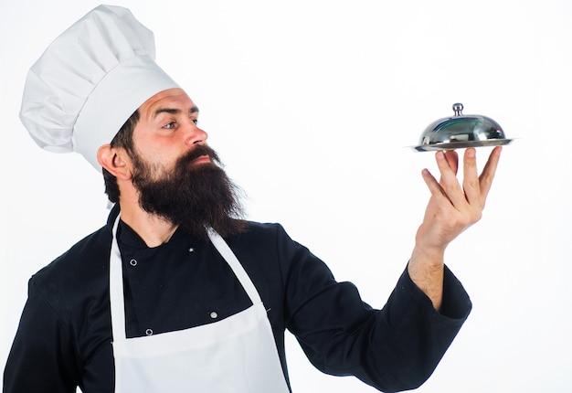 Ristorante servizio e presentazione. chef barbuto con vassoio di cibo. il cuoco tiene il piatto metallico.