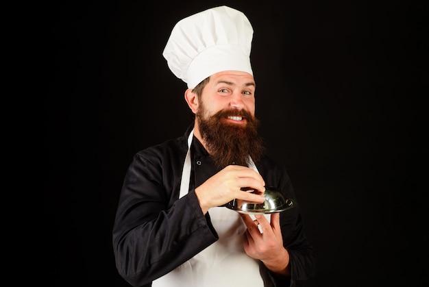 Servizio e presentazione del ristorante. chef maschio con vassoio di cibo. cuocere con cloche nel ristorante.