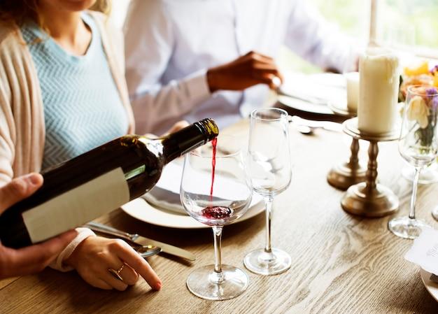Il personale del ristorante poring serve vino rosso ai clienti