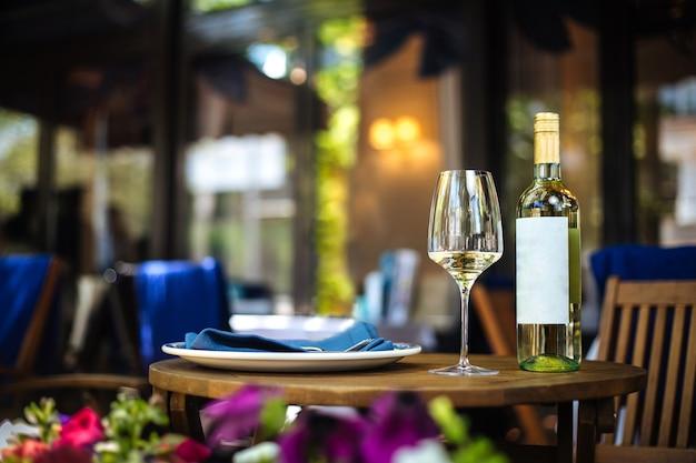 Tavolo in legno terrazza estiva ristorante servito con un piatto di vetro e una bottiglia di vino bianco