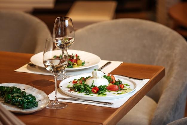 Tavolo ristorante servito con insalate e bicchieri di vino bianco
