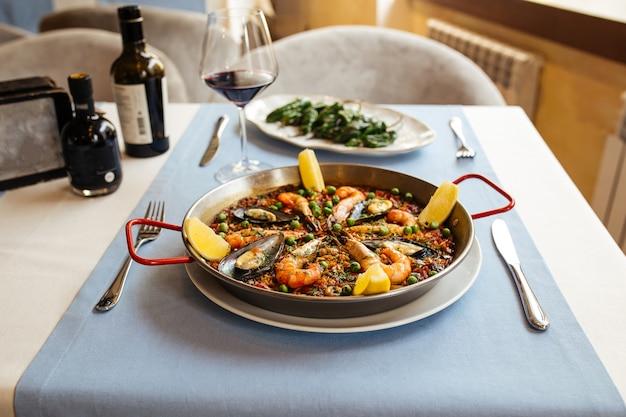Tavolo del ristorante servito con piatti spagnoli, paella di pesce e peperoni padron