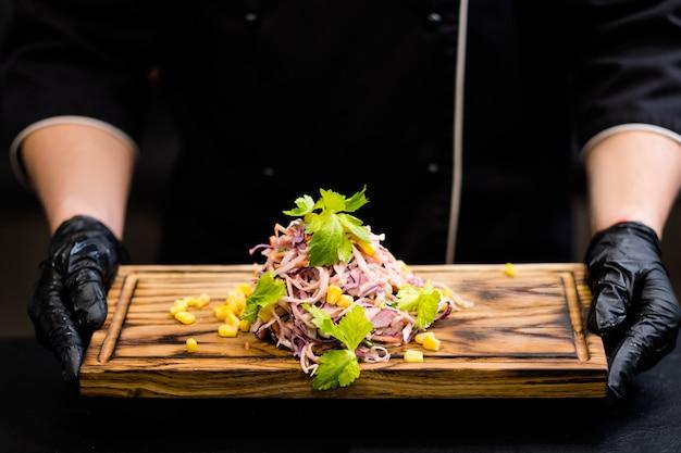 Menu vegetariano del ristorante. ritagliata colpo di chef in guanti da cucina neri che tengono tavola di legno con insalata di cavolo insalata di cavolo.