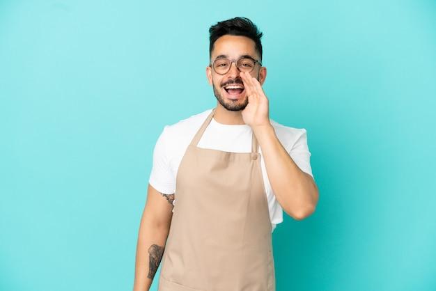 Ristorante cameriere uomo caucasico isolato su sfondo blu che grida con la bocca spalancata