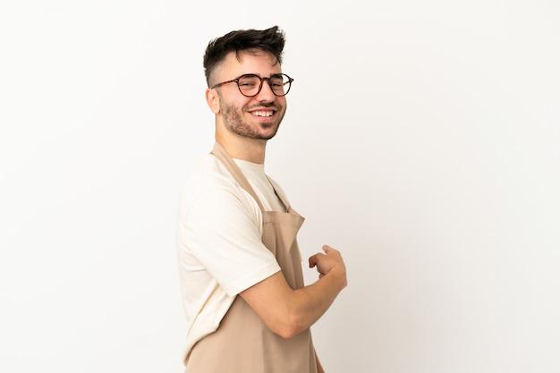 Ristorante cameriere uomo caucasico isolato su sfondo bianco che punta indietro