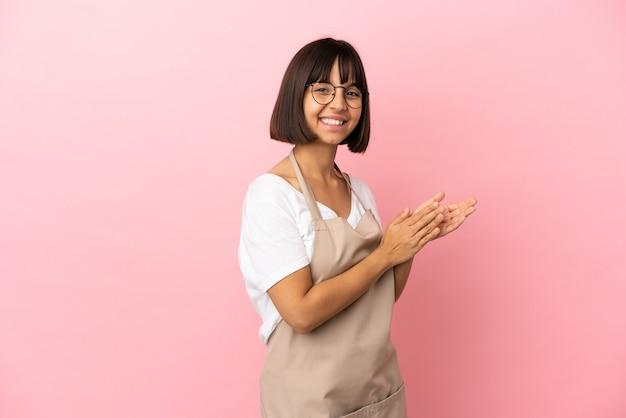 Cameriere del ristorante su sfondo rosa isolato che applaude