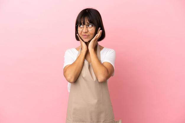 Cameriere del ristorante su sfondo rosa isolato frustrato e che copre le orecchie
