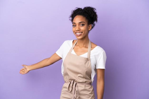 Cameriere del ristorante donna latina isolata su sfondo viola che estende le mani di lato per invitare a venire