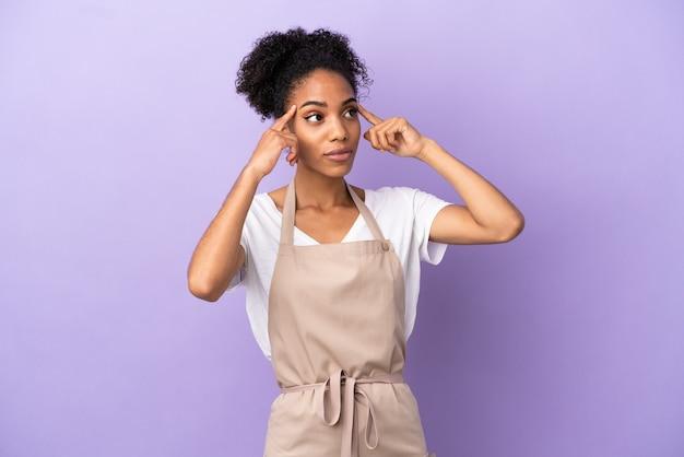 Cameriere del ristorante donna latina isolata su sfondo viola con dubbi e pensieri