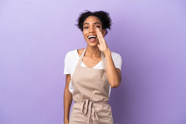 Cameriere del ristorante donna latina isolata su sfondo viola che grida con la bocca spalancata