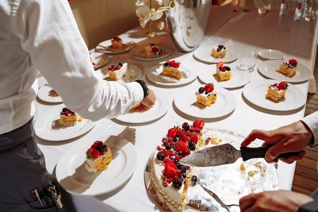 Camerieri del ristorante che tagliano la torta dolce a pezzi per servire gli ospiti in vacanza. le mani si chiudono sulla vista.
