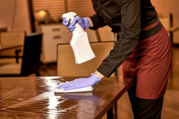 Lavoratore del ristorante che lava un tavolo spruzzato con un panno