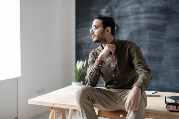 Riposante impiegato maschio in occhiali da vista e abbigliamento casual guardando attraverso la finestra dell'ufficio mentre si siede sul tavolo