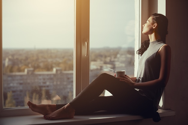Riposo e pensante donna con gli occhi chiusi. ragazza calma con una tazza di tè o caffè seduto sul