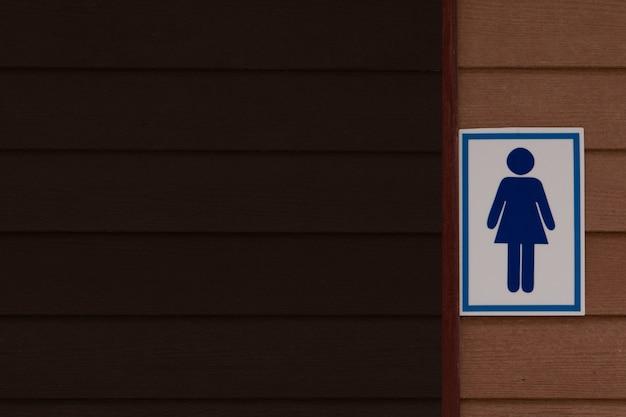 Segno del bagno sulla parete di legno, signora della toletta della signora