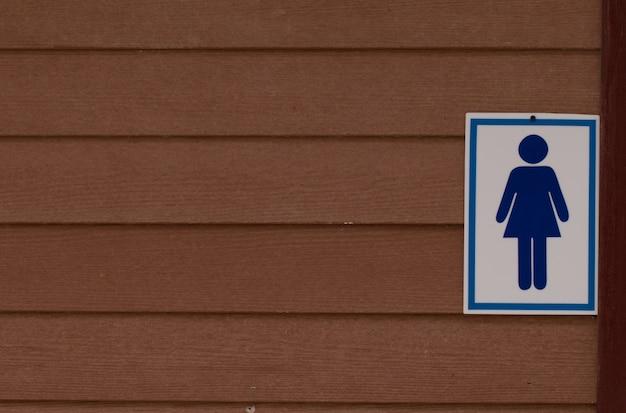 Segno della toilette sulla parete di legno, segno della toilette della signora
