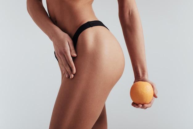 Risultati di fitness. foto di particelle di ragazza in biancheria intima nera in piedi al muro bianco e tenendo l'arancia.