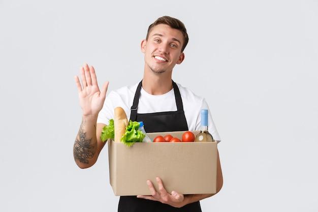 Negozio di generi alimentari al dettaglio e concetto di consegna amichevole bel venditore fatto scatola con generi alimentari...