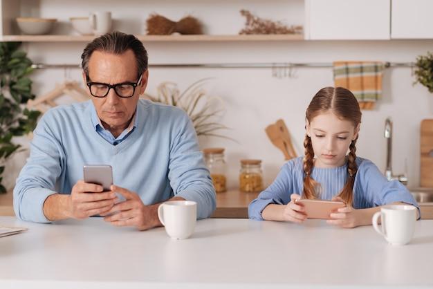 Pensionato invecchiamento dipendente in pensione seduto in casa e utilizza lo smartphone con la nipote mentre naviga in internet e controlla i profili dei social media