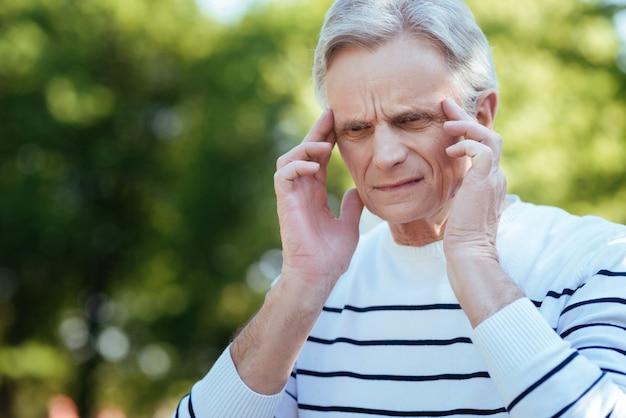 Uomo triste invecchiato in pensione che tocca le sue tempie ed esprime frustrazione mentre soffre di mal di testa all'aperto