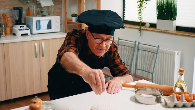 Uomo in pensione fornaio setacciare la farina sul tagliere fare la pasta a casa. chef anziano anziano con bonete e spolverata uniforme, setacciare, distribuire gli ingredienti a mano, cuocere pizza e pane fatti in casa