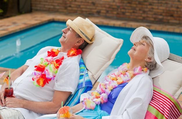Coppia di pensionati dormendo accanto alla piscina