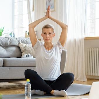 La donna anziana in pensione gode dello yoga di realizzazione personale a casa benessere a casa