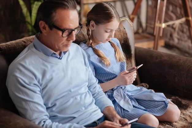 Uomo dipendente indifferente in pensione seduto sul divano e utilizzando cellulari con bambino durante la navigazione in internet