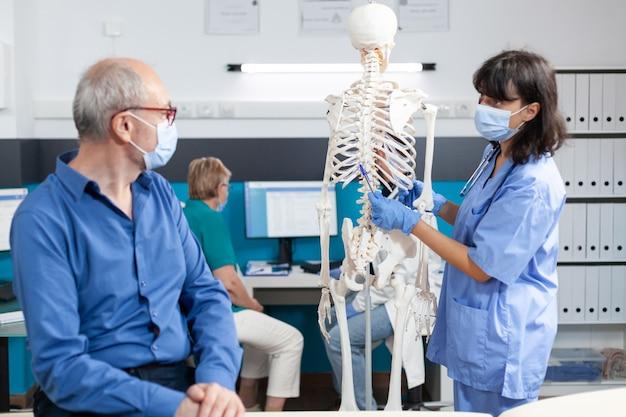 Uomo in pensione che guarda lo scheletro umano per la cura chiropratica
