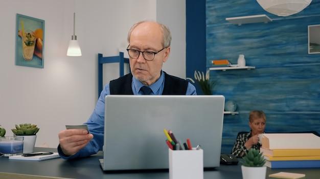 Uomo in pensione che fa shopping online effettuando il pagamento tramite carta di credito su laptop che lavora da casa. persona anziana che paga le bollette, effettua transazioni di e-commerce utilizzando la tecnologia moderna via internet