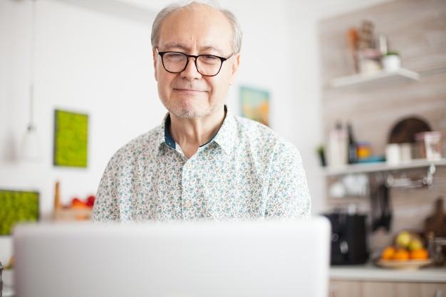 Uomo in pensione che sorride mentre guarda un film sul portatile. la vita quotidiana dell'uomo anziano in cucina durante la colazione utilizzando il computer portatile che tiene una tazza di caffè. anziano pensionato che lavora da casa, telecomunicazioni