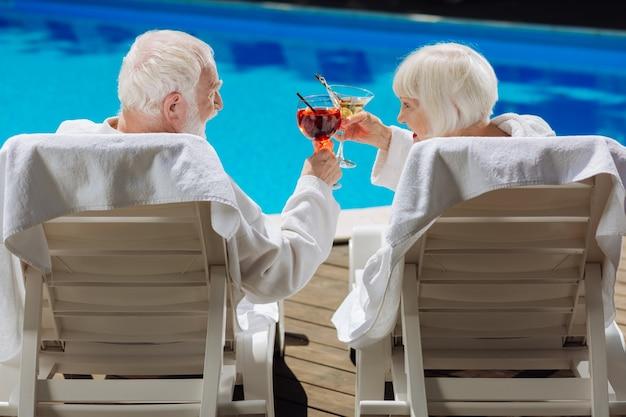Uomo e donna in pensione che si sentono estremamente felici mentre si godono la vita sdraiati vicino alla piscina